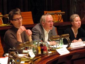 Drei Personen sitzen an einem Pult, die mittlere spricht. Die Frauen links und rechts des Redners schauen geradeaus in Richtung des Ausganges. Vor ihnen stehen Namensschilder.