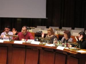 Fünf Personen sitzen nebeneinander in einer Reihe hinter Pulten. Die zweite, mittlere und letzte Person (von links) heben die Hand zur Abstimmung hoch.
