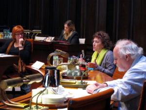 Vier Personen sitzen in zwei Reihen hinter Pulten. Eine Frau spricht und hebt dabei beide Hände auf Schulterhöhe.