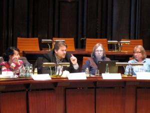 Vier Personen sitzen hinter Pulten, eine Person spricht mit erhobenem Zeigefinger. Die linke Person schaut zum Redner rechts neben ihr, die beiden rechten Personen schauen in ein aufgeklapptes Notebook auf dem Tisch vor sich.