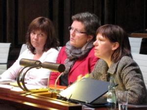 Drei Frauen sitzen nebeneinander hinter Pulten. Die Frau rechts spricht.