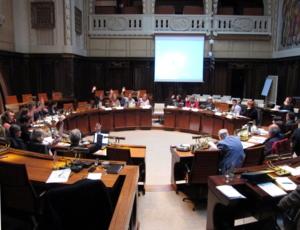 Die Ausschussmitglieder sitzen kreisförmig hinter Pulten im Hodlersaal. Einige heben die Hand zur Abstimmung.