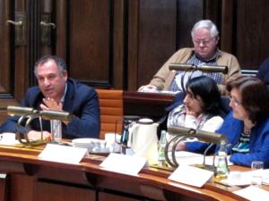 Drei Personen sitzen hinter Pulten. Oben ist noch ein Zuhörer erkannbar, der jedoch nicht zum Ausschuss gehört. Der Mann links im Bild spricht.