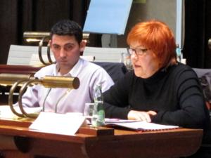 Zwei Personen sitzen hinter Pulten. Die Frau rechts spricht.