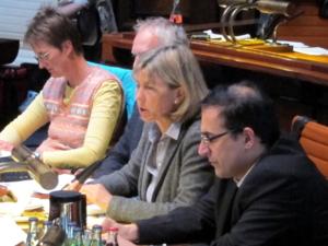 Vier Personen sitzen hinter Pulten. Eine der beiden Frauen spricht.