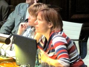 Eine Frau sitzt hinter einem aufgeklappten Notebook und schaut nach vorne. Hinter ihr sind drei weitere sitzende Personen erkennbar.