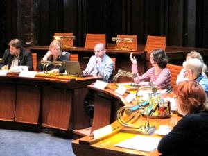 SIeben Personen sitzen im Viertelkreis hinter Pulten. Eine Frau hebt die Hand, um einen Redebeitrag zu signalisieren.