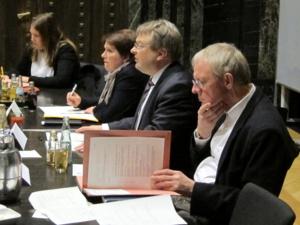 Vier Personen, zwei Frauen und zwei Männer, sitzen nebeneinander an Tischen. Die linke Frau schreibt, die zweite Frau hält eien Stift in der Hand und schaut nach vorne - ebenso wie der linke der beiden Männer. Der rechte Mann blättert in einer Aktenmappe, die vor ihm auf dem Tisch liegt.