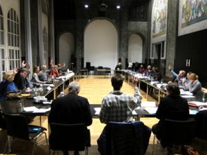 Im Mosaiksaal sind mehrere Tische U-Förmig aufgestellt, an denen die Ausschussmitglieder sitzen.