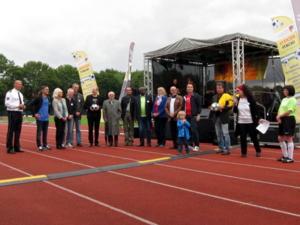 16 Personen stehen vor einer Bühne.