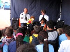 Etwa 20 Kinder sitzen in einem Zelt. Vor ihnen sitzen eine Polizist und eine Polizistin mit Handpuppen.