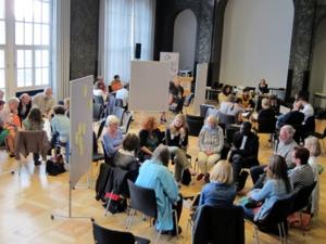 Kritische Textanalysen, Ideen- und Erfahrungsaustäusche bei Workshops mit Fachleuten. Die Teilnehmer sitzen in Stuhlkreisen und arbeiten miteinander.