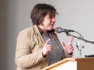 Eine Frau steht am Rednerpult hinter einem Mikrofon und spricht. Dabei hebt sie beide Zeigefinger hoch.