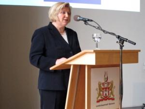 Eine Frau steht hinter einem Rednerpult und spricht.