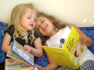 Zwei Kinder sitzen nebeneinander und schauen sich Bücher an