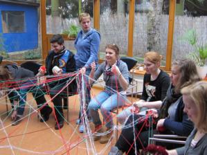 Eine Gruppe von Jugendlichen sitzt im Kreis, wobei jeder von Ihnen untereinander gespannte Fäden in der Hand hält