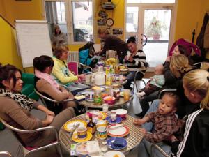 Mehrere junge Frauen sitzen mit ihren kleinen Kindern an Tischen, auf denen Frühstücksutensilien stehen