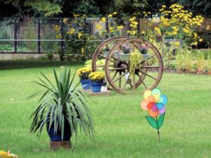 Ein mit Blumen geschmücktes Holzrad im Park des Pflegezentrums Heinemanhof