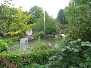 Beete und Rasenfläche eines Kleingartens stehen unter Wasser