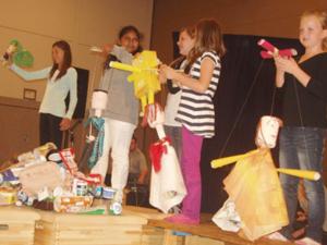 Schulkinder zeigen selbstgebastelte Marionetten aus Abfallmaterial