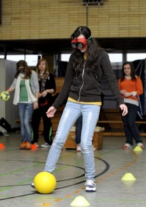 Ein junge Frau bewältigt einen Hindernisparcours mit Rauschbrille