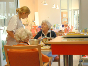 Seniorinnen und eine Helferin beim Kartoffelschälen