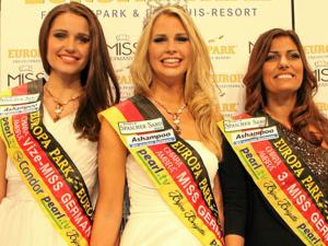 Zwei dunkelhaarge und eine blondhaarige Frauen mit Schärpen in den Bundesfarben, die in die Kamera lächeln.