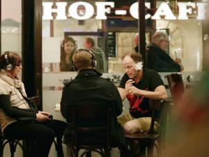 Drei Menschen sitzen vor einem Café und unterhalten sich.