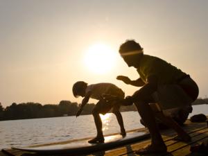 Ein Junge und ein Mann stehen auf einem Surfbrett auf einem Steg.