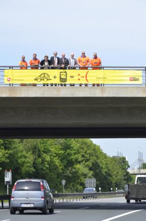Spannband an Brücke mit Menschen dahinter über vierspuriger Straße