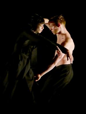 Frau im schwarzen Mantel und Mann mit freiem Oberkörper.