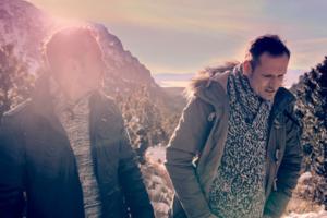 Zwei Männer vor einem Berg.