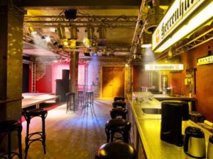 Leerer Musikclub mit Tresen und Barhockern davor.