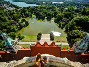 Blick vom oben auf eine Parklandschaft mit einem Teich und einem See dahinter.