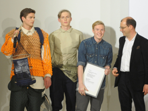 Mehrere Männer stehen nebeneinander; einer hält ein weißes Plakat in der Hand