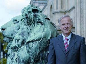 Ein Mann steht neben einen Löwen-Statue.