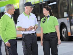 Eine Frau und zwei Männer stehen vor einem Bus