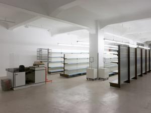 In einer Halle sind leere Regale sowie eine leer Supermarktkasse aufgestellt.