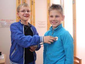 Zwei Jungen, der eine horcht den anderen mit einem Stethoskop ab.
