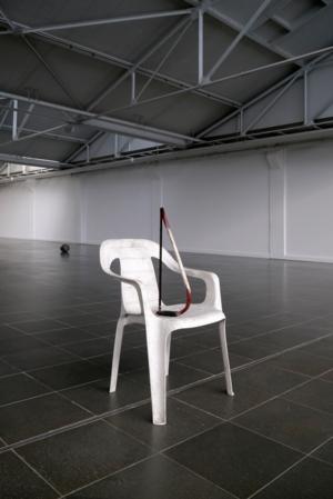 Eine Säge auf einem Plastikstuhl in einer fast leeren Halle.