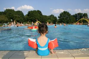 Mädchen mit Schwimmflügeln sitzt mit dem Rücken zum Betrachter am Beckenrand. Im Freibad plantschen viele Kinder.