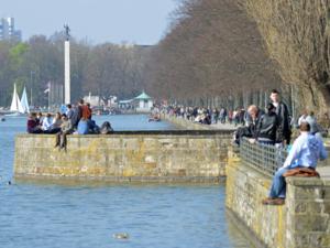 Menschen am Ufer eines Sees.