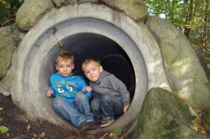 Zwei kleine Jungen erkunden eine Betonröhre