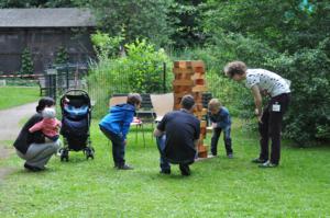 Kinder und Erwachsene beim Jenga-Spiel