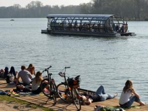 Ein Solarboot und Menschen am Ufer eines Sees.