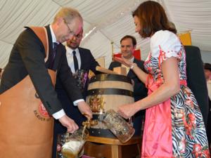 Ein Mann füllt Bier aus einem Bierfass in ein Bierglas, rechts daneben steht eine Frau mit einem weiteren Glas.