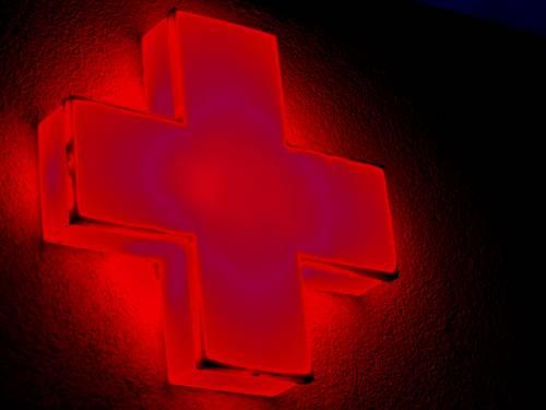 In rot leuchtet ein Kreuz oder Plus-Zeichen an einem Gebäude.