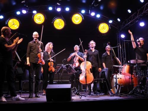 Eine Musikerin und sechs Musiker verabschieden sich nach einem Auftritt.