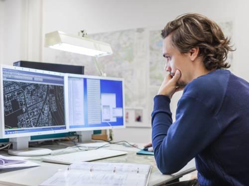 Ein Mann sitzt an einem Schreibtisch vor zwei Bildschirmen