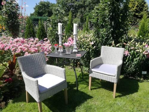 Blick in einen Garten, in dem ein Tisch mit zwei Stühlen steht. Auf dem Tisch stehen Kerzen und Getränke.
